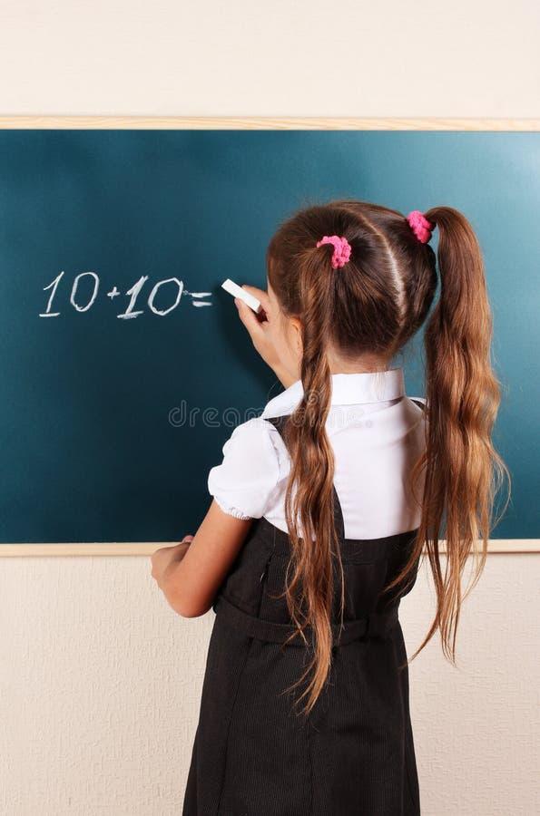 Beautiful little girl writing on board stock photo