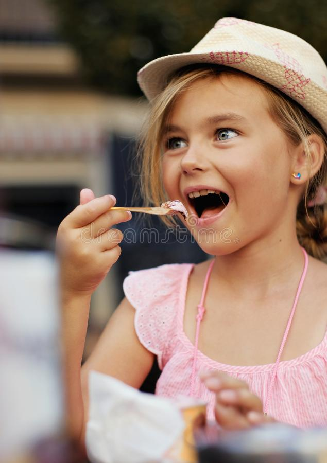 Beautiful little girl eating ice-cream sitting in outdoors cafe royalty free stock photos