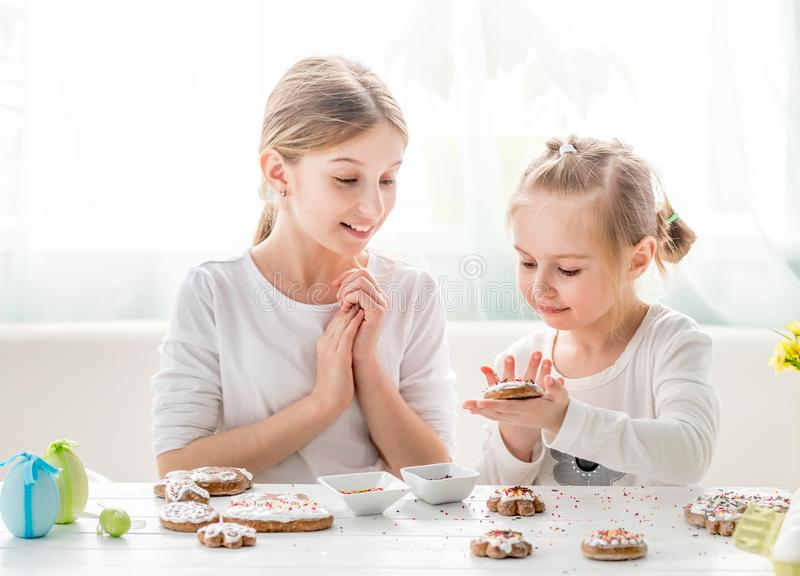 Girls decorating homemade gingerbread cookies. Beautiful little girls decorating homemade gingerbread cookies with glaze and colorful dragee stock images