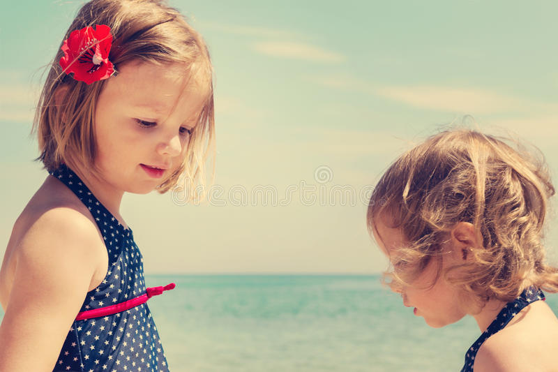 Beautiful little girls (sisters) play in the sea. The image is tinted royalty free stock photos