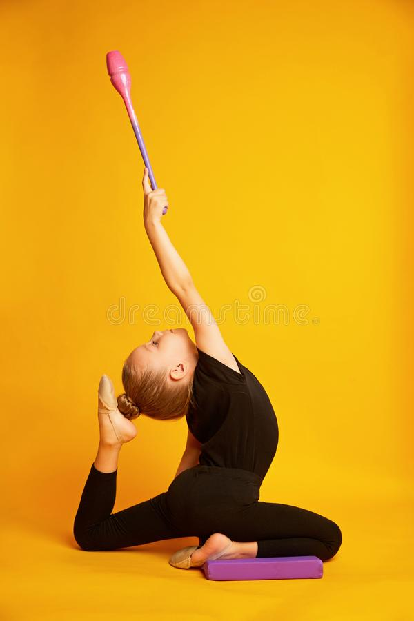 Beautiful little gymnast in black sportswear with gymnastic maces shows exercises on a yellow background. stock images