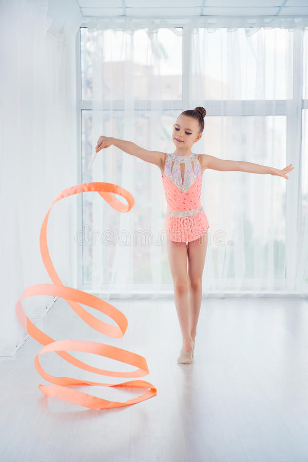Beautiful little gymnast girl in pink sportswear dress, doing rhythmic gymnastics exercise Spirals with art ribbon stock photo