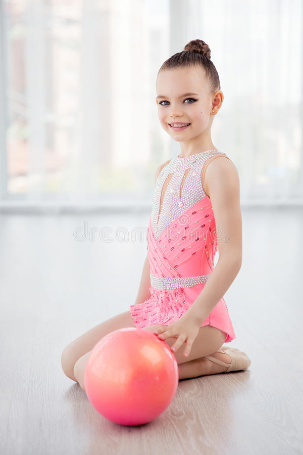 Beautiful little gymnast girl in pink sportswear dress, performing art gymnastics element with ball in fitness class. Portret of beautiful little gymnast girl in royalty free stock photo