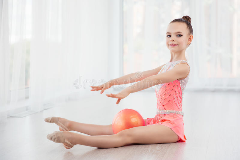 Beautiful little gymnast girl in pink sportswear dress, performing art gymnastics element with ball in fitness class. Beautiful little gymnast girl in pink stock photography