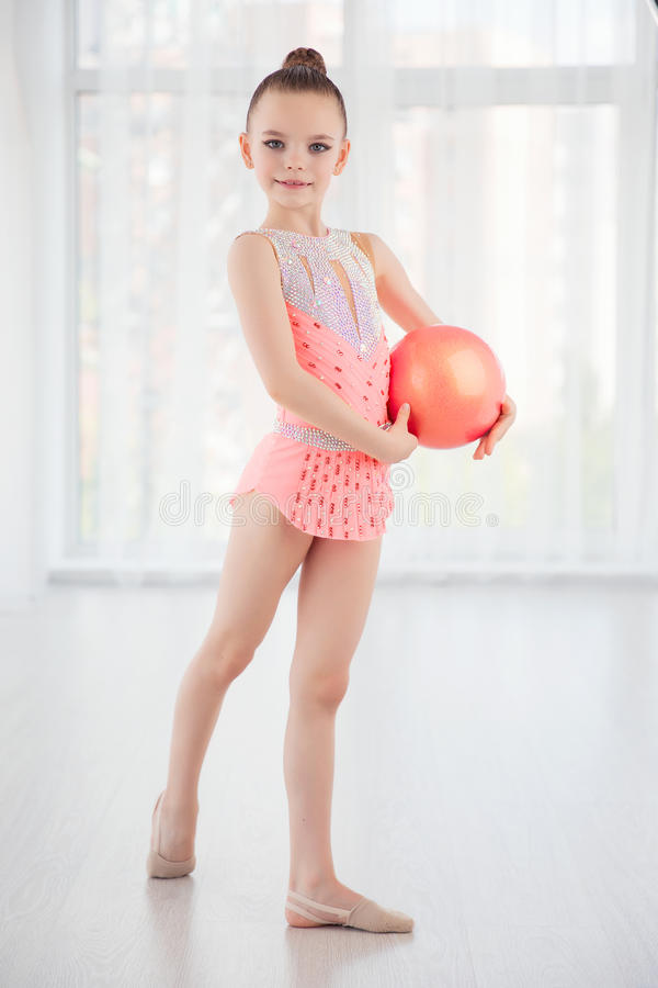Beautiful little gymnast girl in pink sportswear dress, performing art gymnastics element with ball in fitness class. Beautiful little gymnast girl in pink stock photo