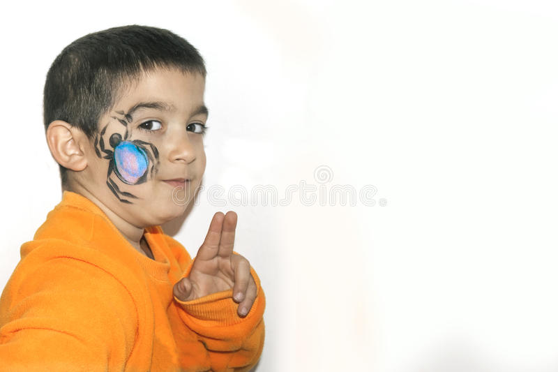 Beautiful little kid boy with face painted with a spider stock photography