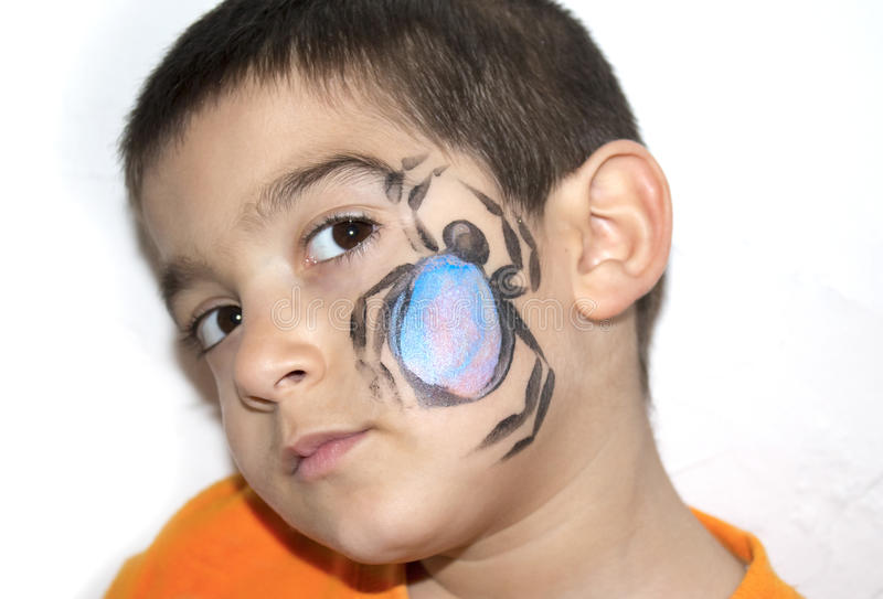 Beautiful little kid boy with face painted with a spider royalty free stock photo