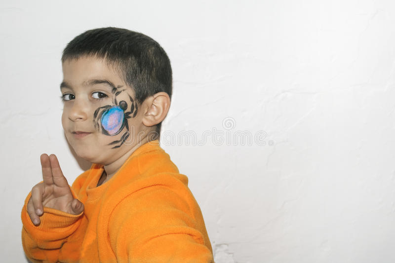 Beautiful little kid boy with face painted with a spider stock photos