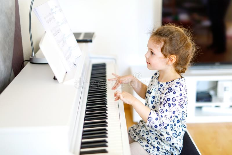 Beautiful little kid girl playing piano in living room or music school. Preschool child having fun with learning to play royalty free stock image