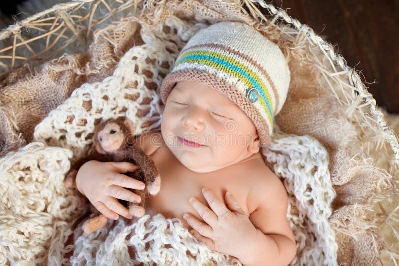 Beautiful little newborn boy 20 days  sleeps in a basket. Portrait of pretty smiling newborn boy stock photos