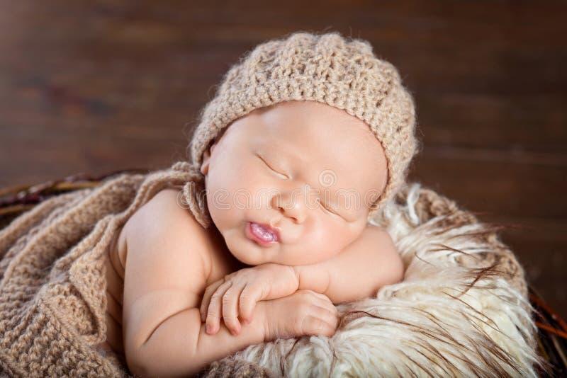 Beautiful little newborn boy 20 days  sleeps in a basket whith knitted plaid. Portrait of pretty newborn boy. Happy family stock photo