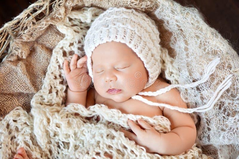 Beautiful little newborn boy 20 days  sleeps in a basket whith knitted plaid. Portrait of pretty newborn boy. Happy family stock image