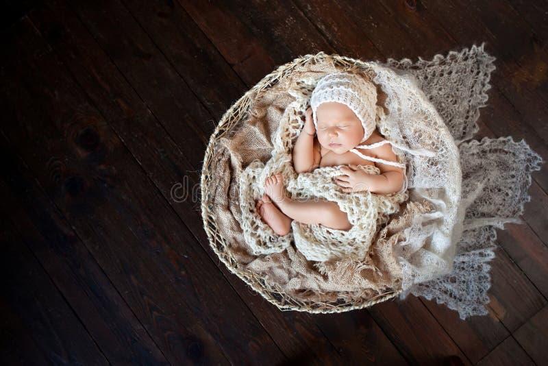 Beautiful little newborn boy 20 days  sleeps in a basket whith knitted plaid. Portrait of pretty newborn boy. Happy family royalty free stock photo