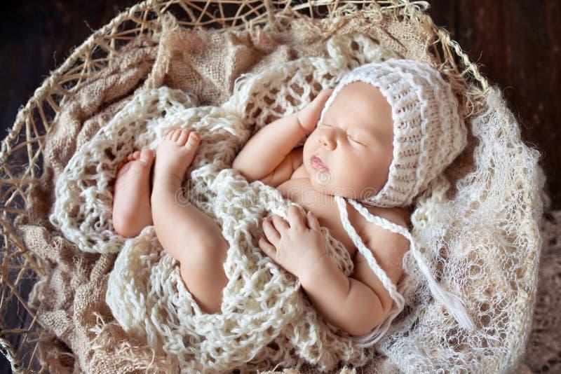 Beautiful little newborn boy 20 days  sleeps in a basket whith knitted plaid. Portrait of pretty newborn boy. Happy family royalty free stock photos