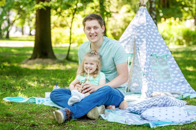 Beautiful little preschool girl playing with dad in the park.The stock photos