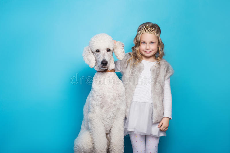 Beautiful little princess with dog. Friendship. Pets. Studio portrait over blue background. Beautiful little princess with dog. Pets. Studio portrait over blue stock image