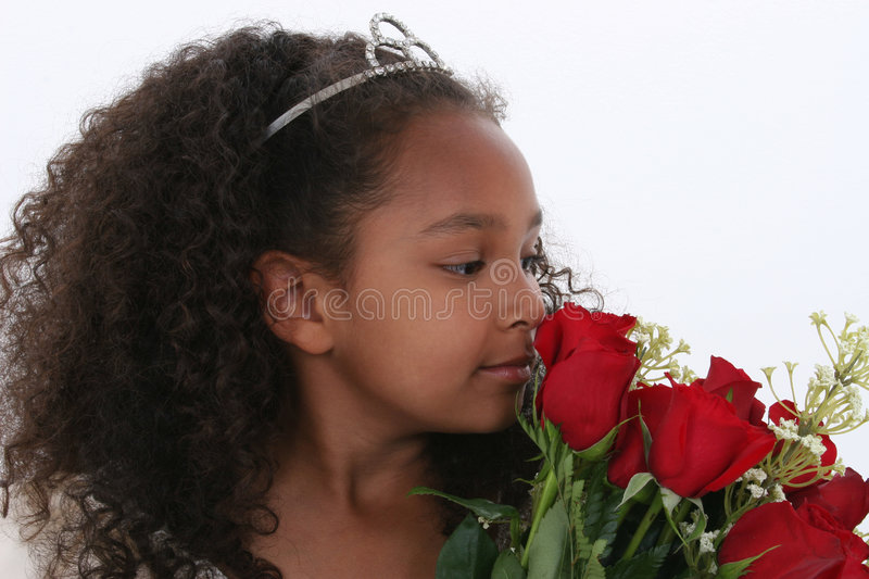 Beautiful Little Princess With Tiara Smelling Roses Over White stock photo
