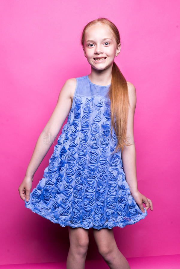 Beautiful little redhead girl in blue dress posing like model on pink background. Beautiful little redhead girl in blue dress posing like model on pink stock photography