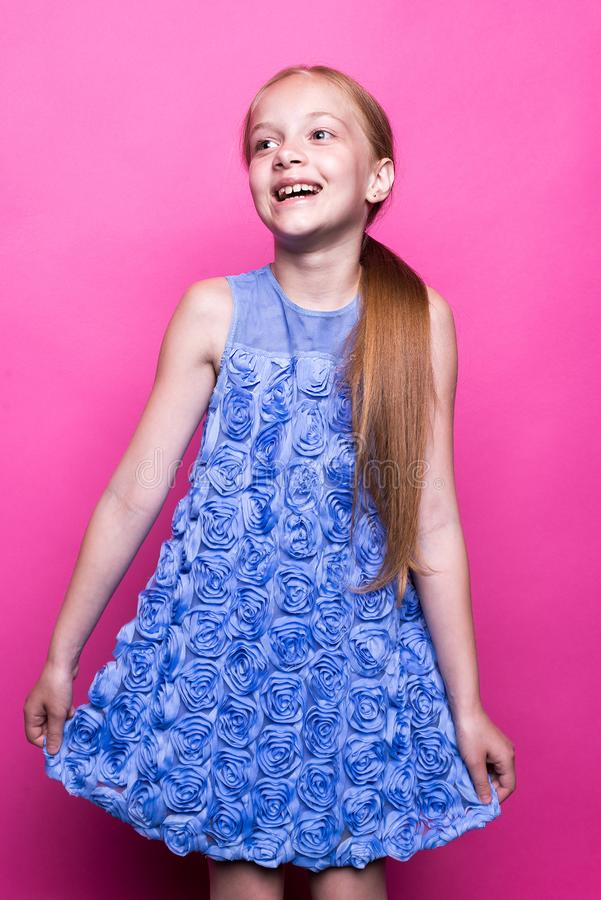 Beautiful little redhead girl in blue dress posing like model on pink background. royalty free stock photography