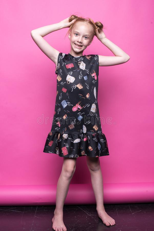 Beautiful little redhead girl in dress posing like model on pink background. Beautiful little redhead girl in dress posing like model on pink background royalty free stock photography