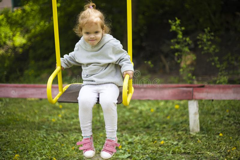 Beautiful little redhead girl riding a swing on the playground royalty free stock images