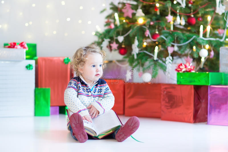Beautiful little toddler girl reading a book under Christmas tree stock photos