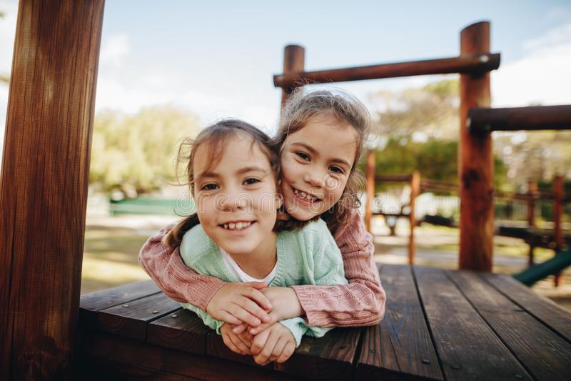 Beautiful little twin girls enjoying at playground stock photos