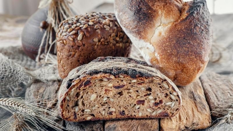 Beautiful loaves of wheat leaven bread with an assortment of grains and seeds on a plate on the edge of the canvas. Homemade cakes royalty free stock photography