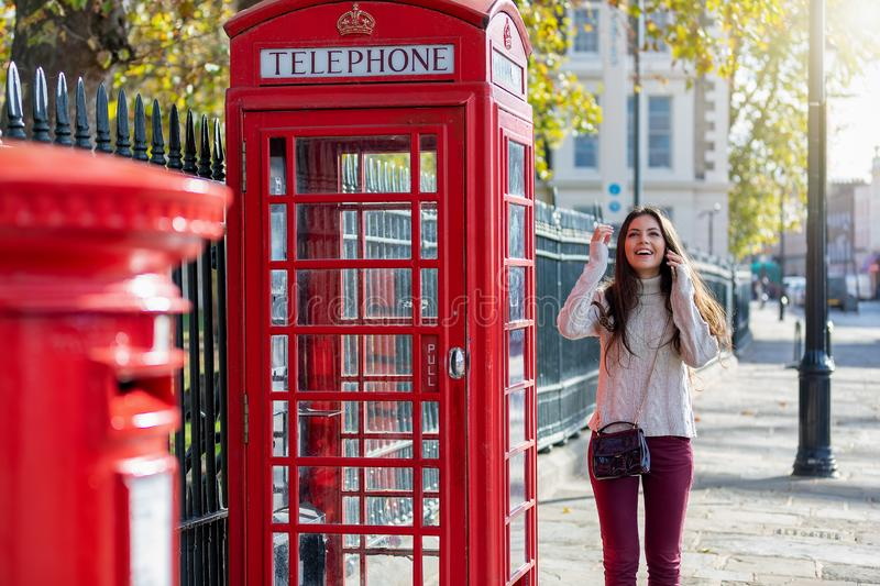 Beautiful London traveler woman stands next to a red telephone booth. And talking to her phone during sightseeing stock image