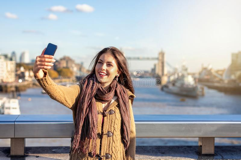 London traveler woman takes selfie photos in front of the famous Tower Bridge. Beautiful London traveler woman takes selfie photos in front of the famous Tower stock photo