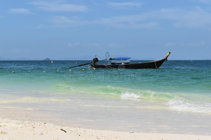 Beautiful lonely beach at Poda Island and a wooden long-tail boat in Krabi, Thailand, Asia. Beautiful lonely beach at Poda Island in Krabi, Thailand in Asia stock photography