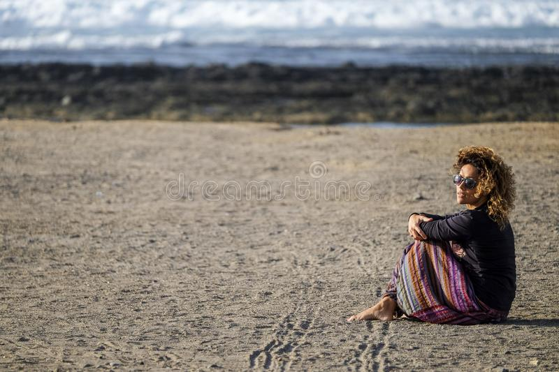 Beautiful lonely caucasian middle age woman walk and enjoy the nobody beach in season. freedom and alternative lifestyle concept stock photo