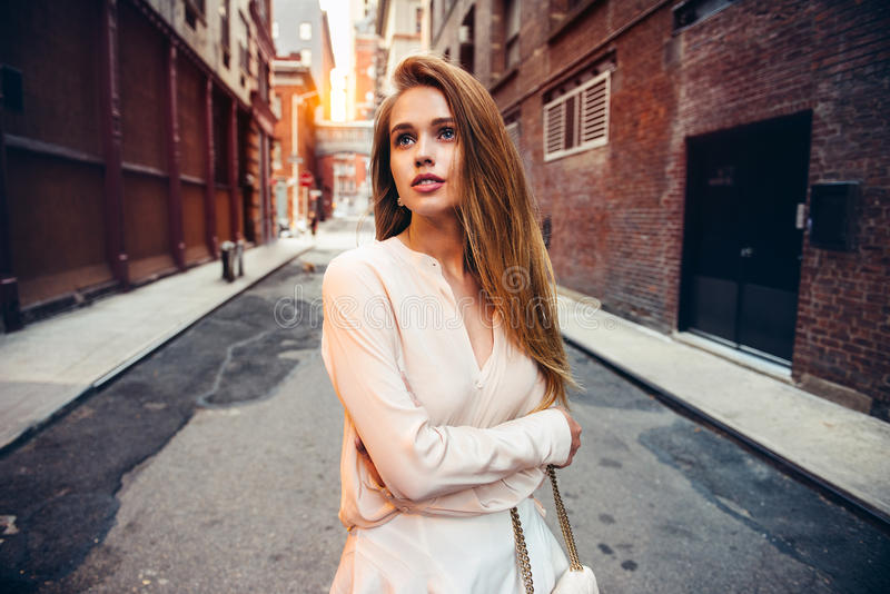 Beautiful lonely girl walking on empty city street looking up to the side. City urban people lifestyle concept stock photos