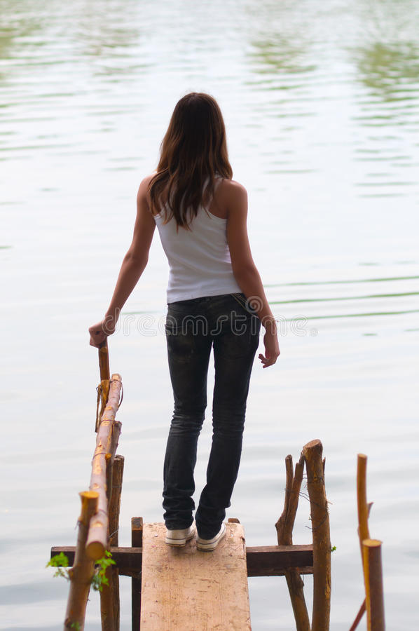 Beautiful lonely teenage girl standing on the dock stock images