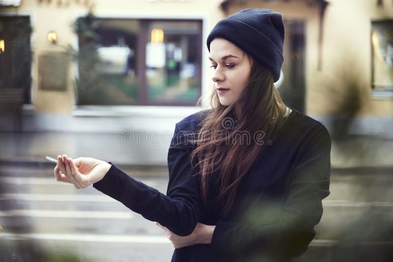 Beautiful lonely woman smoke outside at the street, cold weather in a city. Beautiful lonely woman smoke outside at the street, cold weather in a city royalty free stock photography