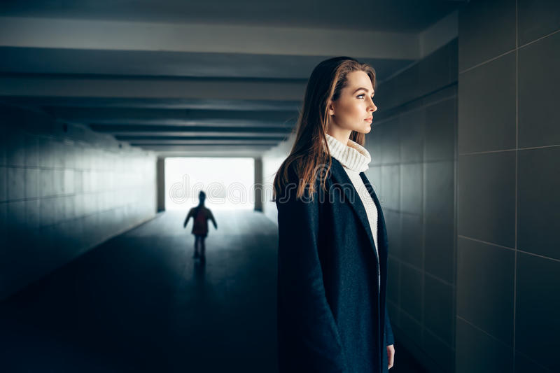 Beautiful lonely woman in subway tunnel with frighten silhouette stock photo
