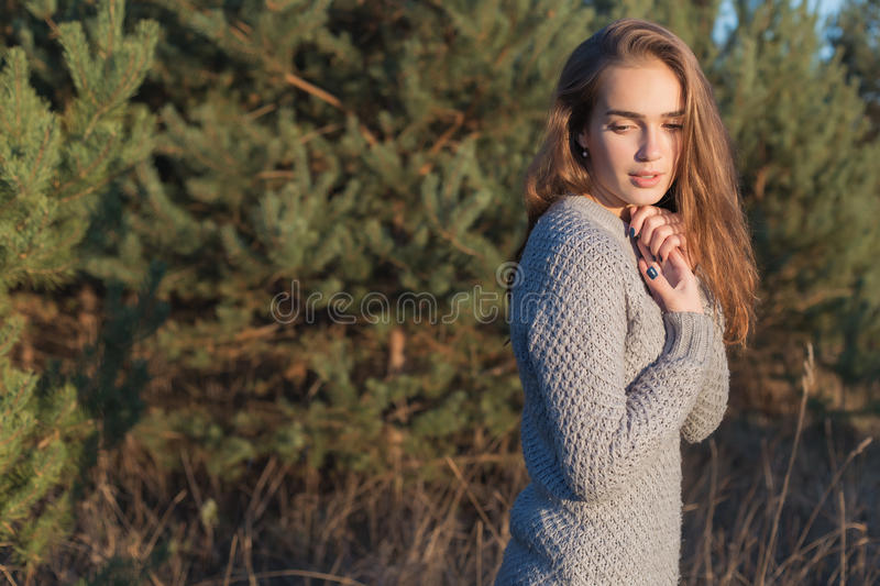 Beautiful lonely young girl with big eyes and wide bushy eyebrows in a warm sweater walking in the forest at sunset stock photos