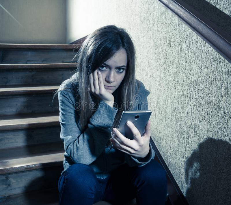 Beautiful lonely young girl depressed and worried suffering from bullying and harassment at school. Teenager girl victim of online stalker suffering from royalty free stock photography