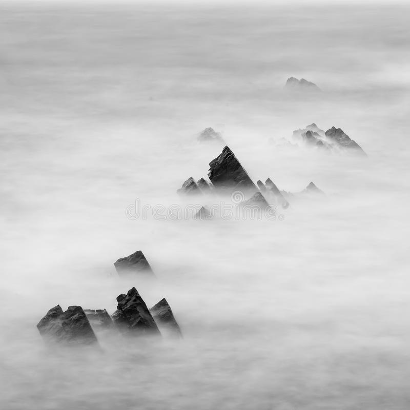 Beautiful long exposure landscape image of sea over rocks during stock photos