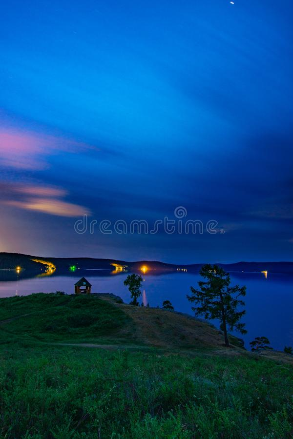 Beautiful long exposure landscape view of the mountain lake Turgoyak, Russia. With cloudy sky and summer house on the hill in summer night, sunrise, evening royalty free stock image