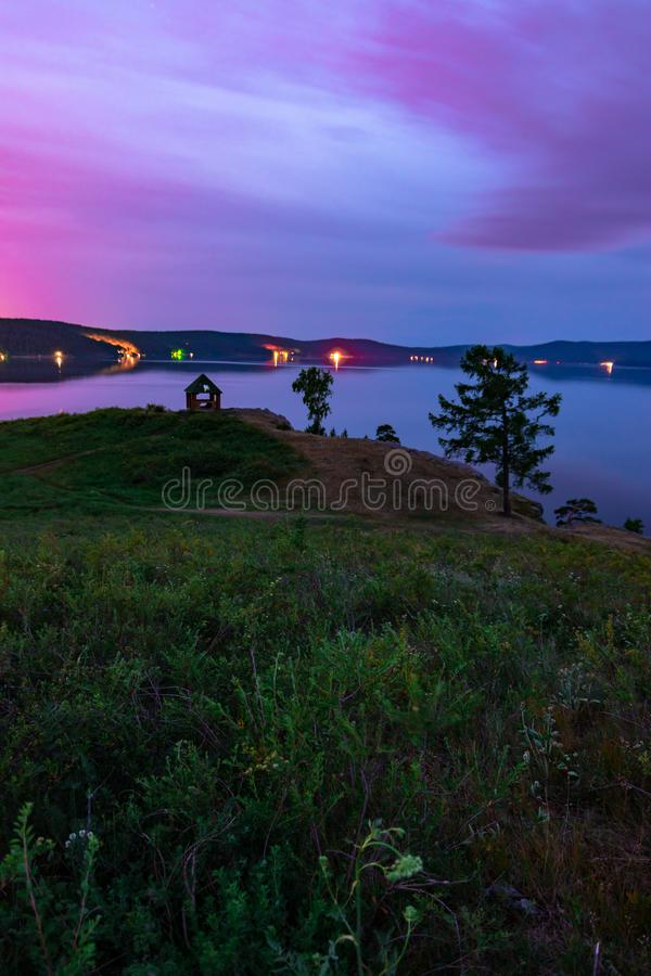 Beautiful long exposure landscape view of the mountain lake Turgoyak, Russia. With purple sky and summer house on the hill in summer night, sunrise, evening royalty free stock image