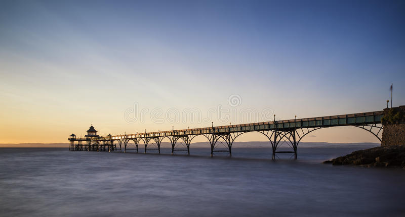 Beautiful long exposure sunset over ocean with pier silhouette. Stunning long exposure sunset over ocean with pier silhouette royalty free stock photography