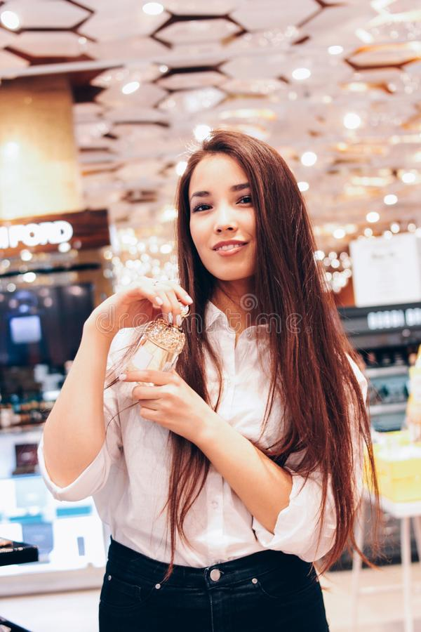 Beautiful long hair asian smiling girl young woman in shop supermarket of cosmetics, perfumes, duty free. The beautiful long hair asian smiling girl young woman royalty free stock images
