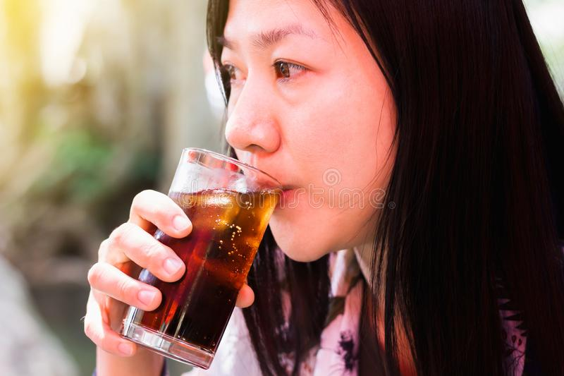 Long hair Asian women drinking black soda in summer day light stock photos