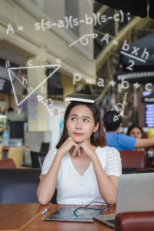 Beautiful long hair Asian woman in a white dress put a black book over her head sitting in coffee shop, touch chin thinking about. Homework from collage stock photo