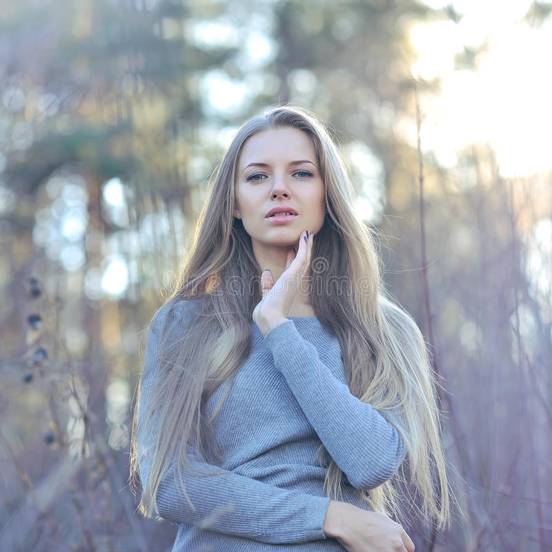 Beautiful long hair blonde woman touching her face. Outdoor fashion portrait.  royalty free stock image