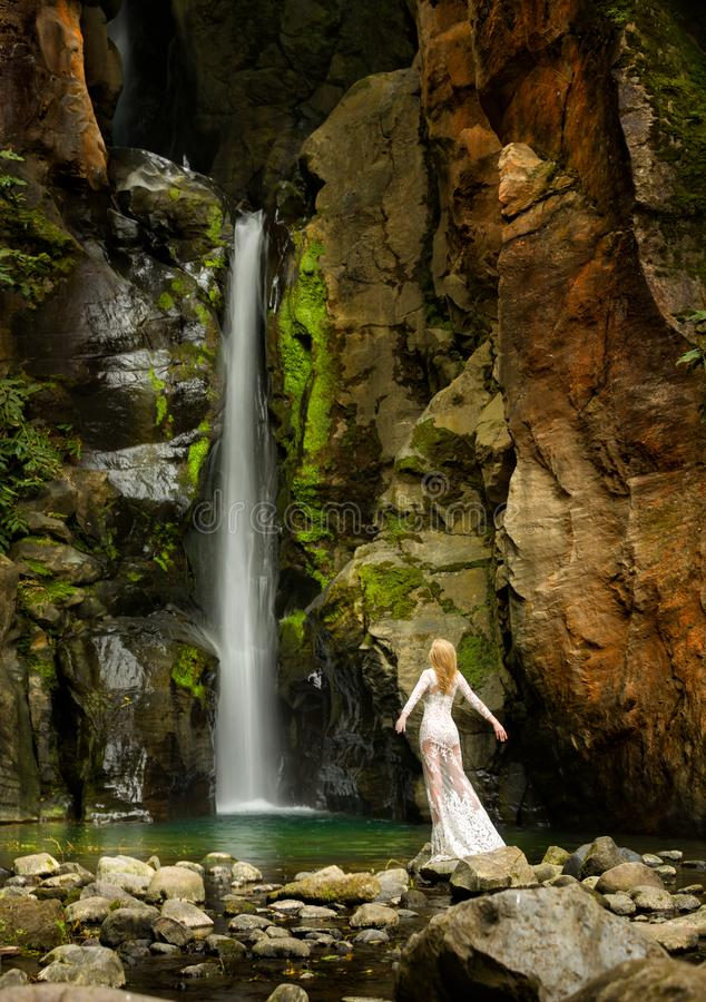 Beautiful long hair blonde woman in white lace dress stands under a waterfall, in Azores Islands. Colorful rocks, and attractive long exposure cascade with a stock photos