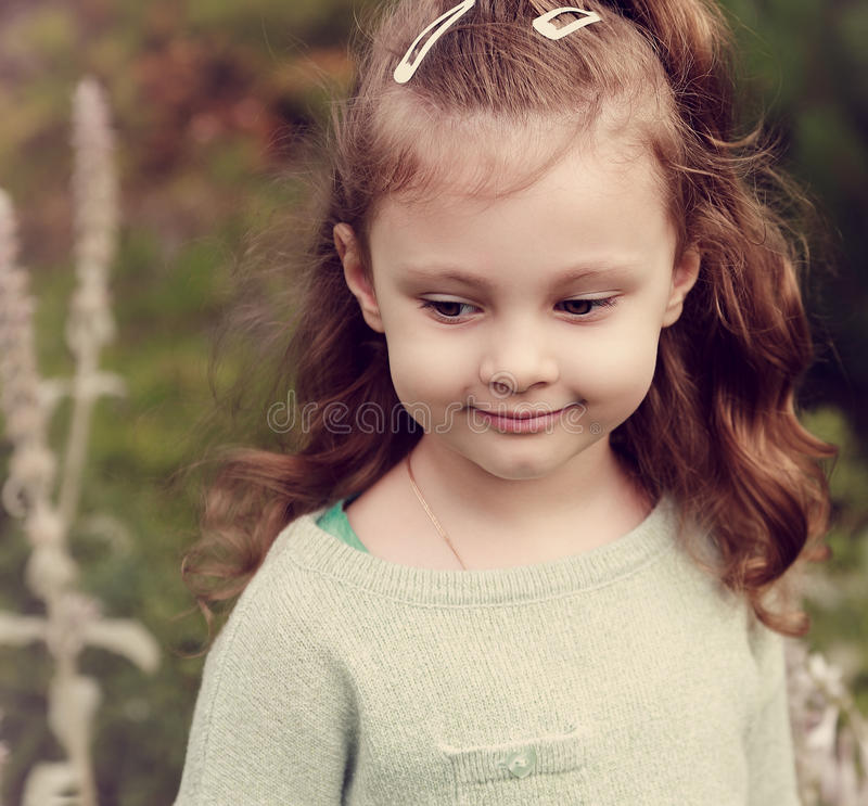 Beautiful long hair kid girl walking in the summer field and sm royalty free stock photography