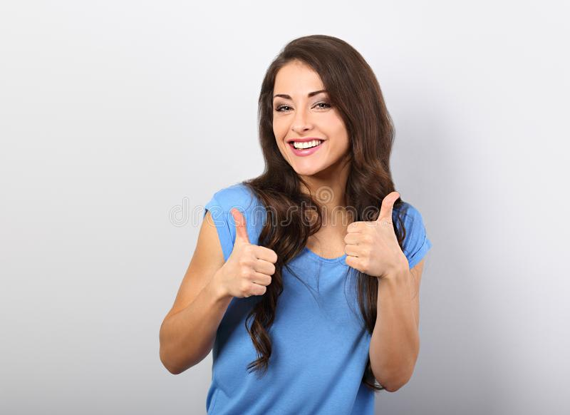 Beautiful long hair smiling woman showing fingers thumb up, the stock photography