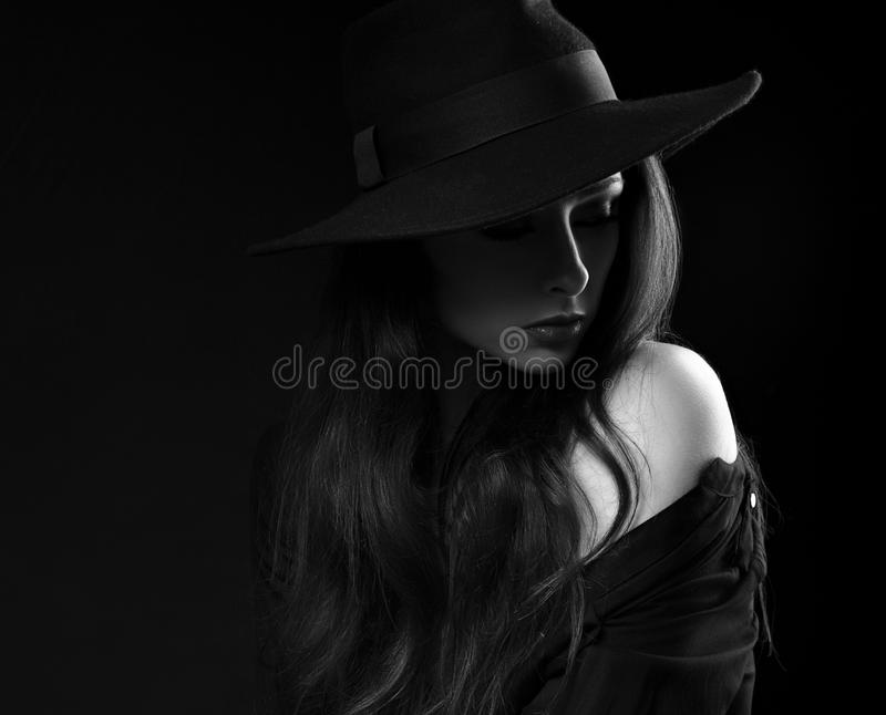 Beautiful long hair woman posing in black shirt and fashion elegant hat in dramatic light on dark shadow background. Closeup art. Portrait. Black and white royalty free stock photography